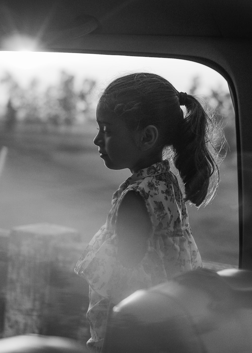 girl in white floral dress sitting on car seat
