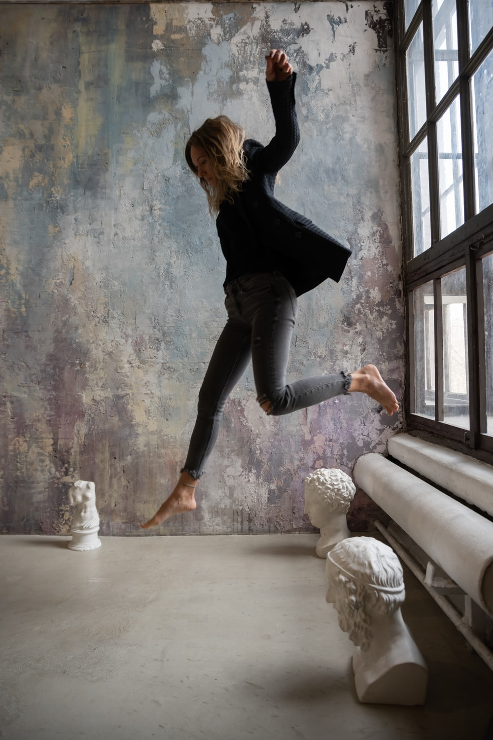 woman in black long sleeve shirt and blue denim jeans jumping on white concrete floor