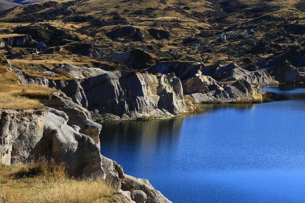 brown rocky mountain beside blue lake during daytime