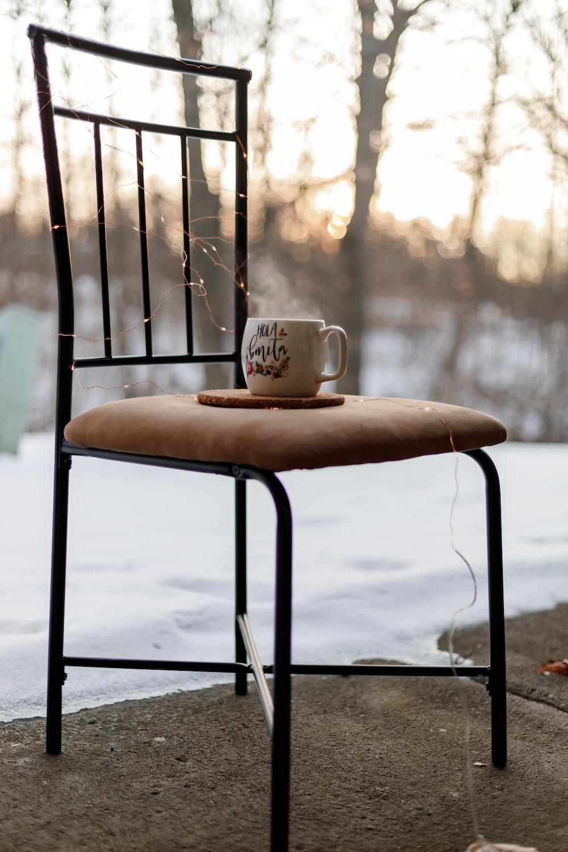 white ceramic mug on brown wooden chair