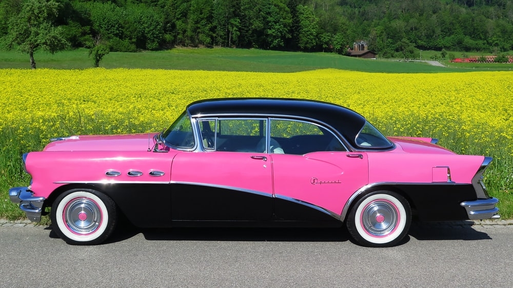 pink vintage car on green grass field during daytime