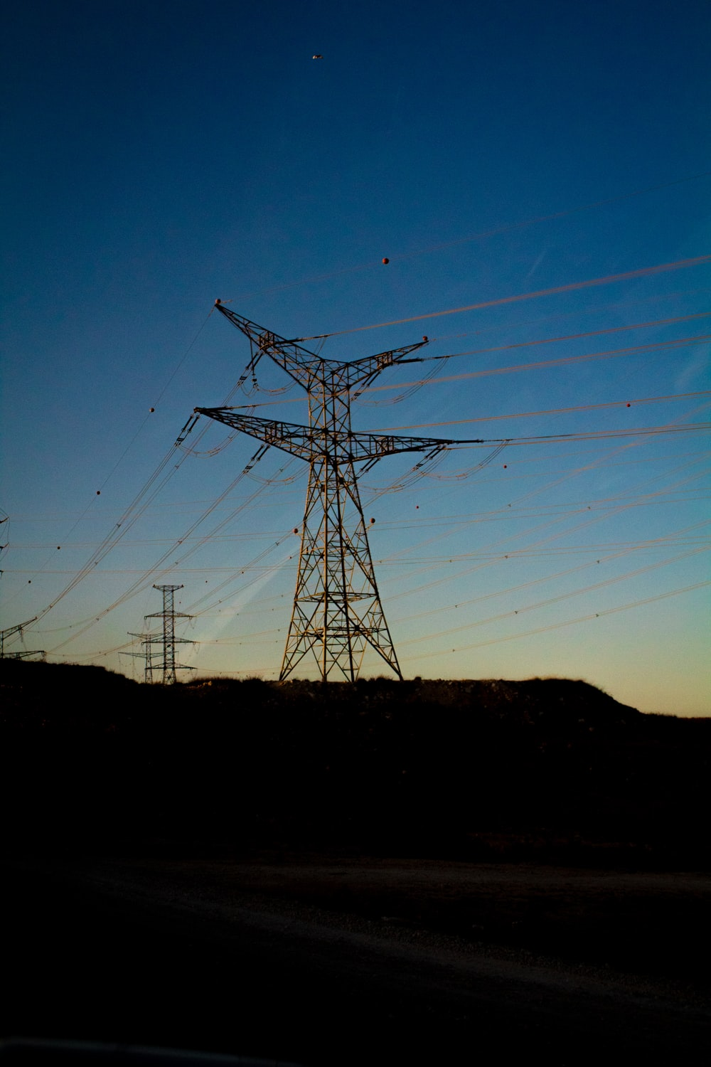 gray electric towers on brown hill under blue sky during daytime