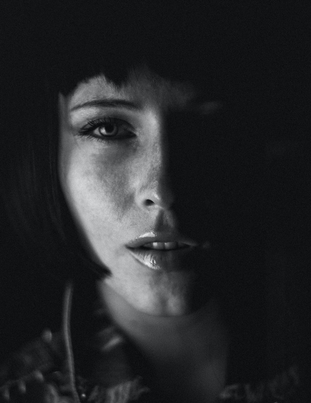 grayscale photo of woman with black background