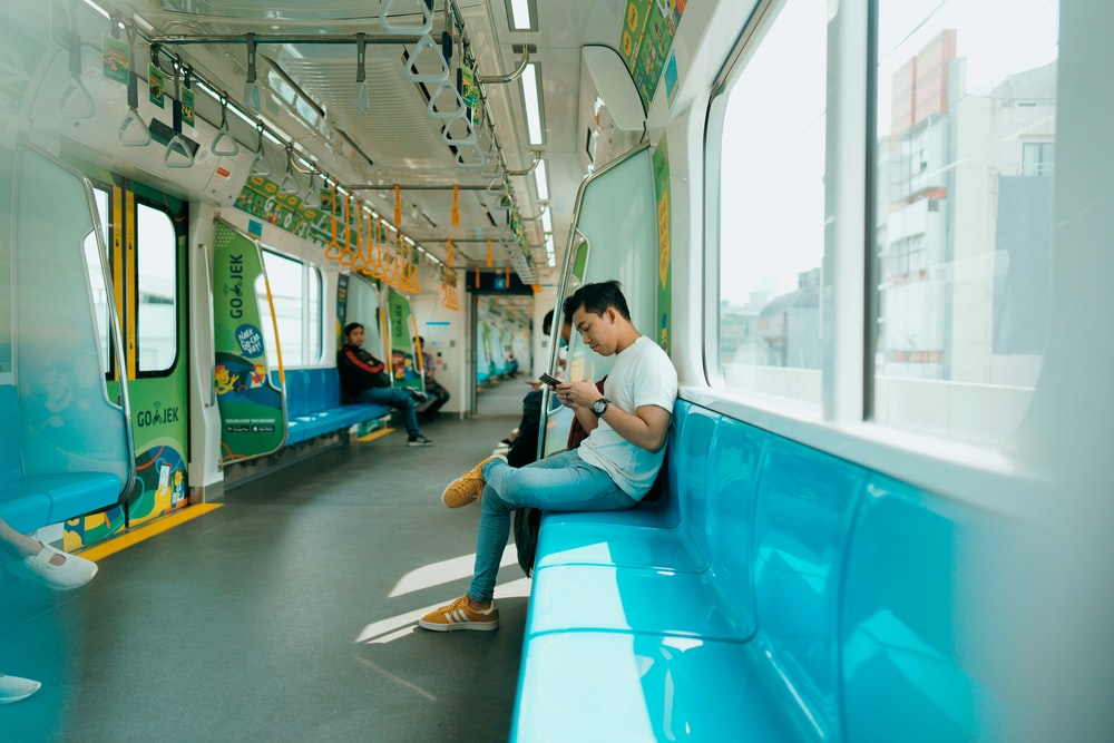 woman in white shirt sitting on blue train seat