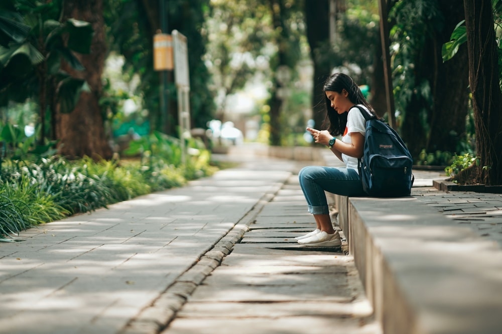 woman in black jacket and blue denim jeans sitting on concrete pathway during daytime
