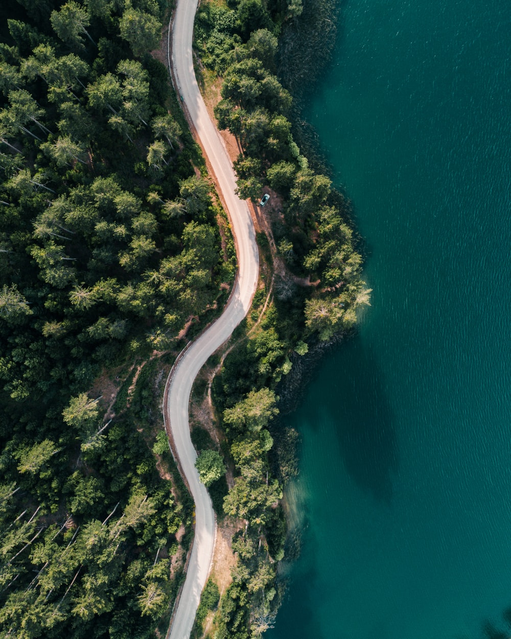 aerial view of road beside body of water during daytime