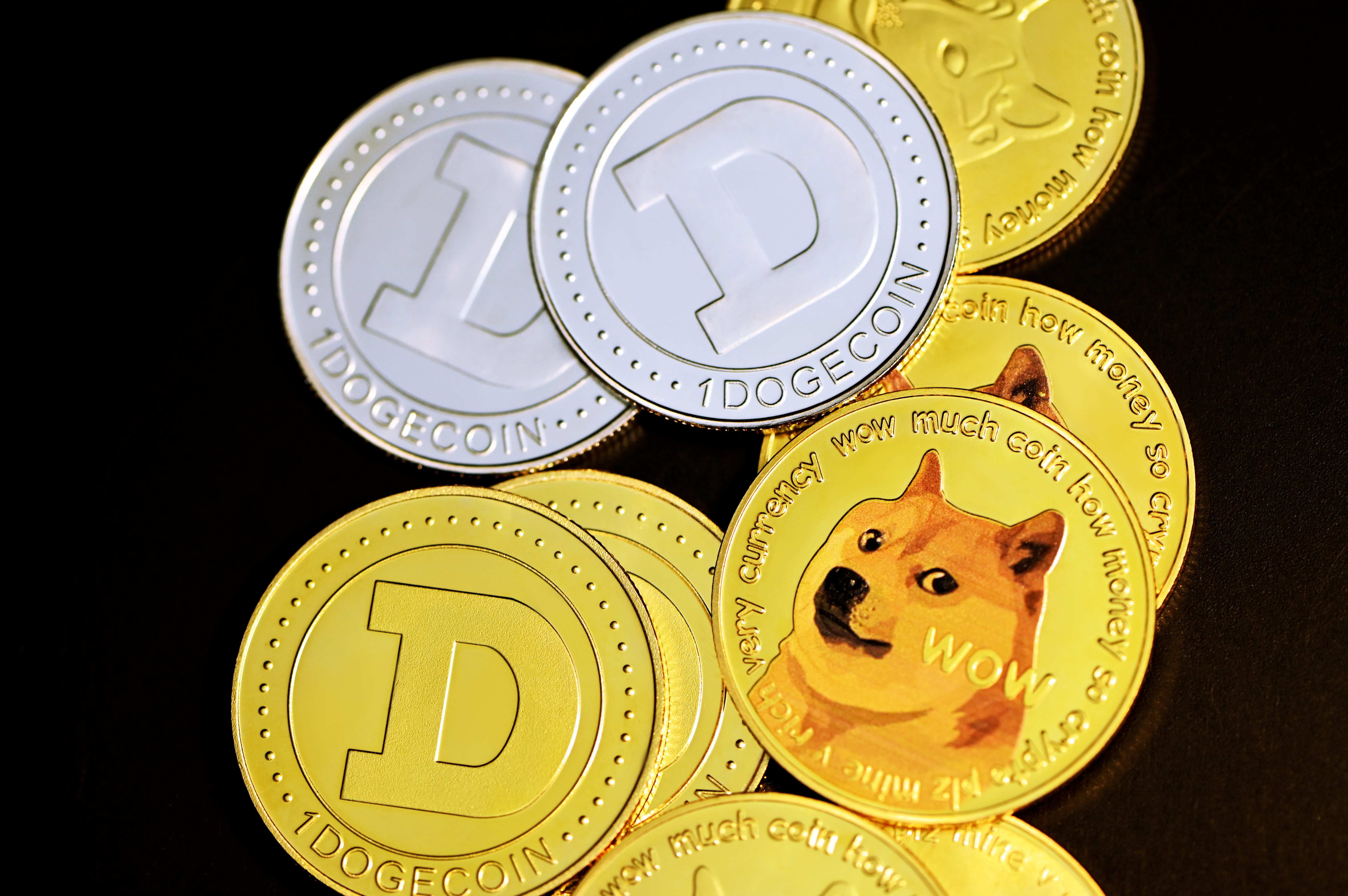 A pile of scattered Dogecoins on top of a black background.