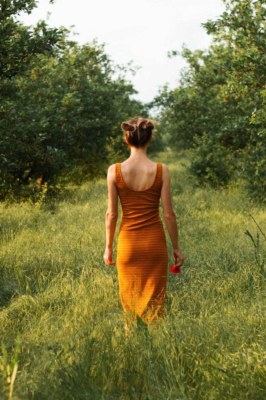 woman in orange tank dress standing on green grass field during daytime