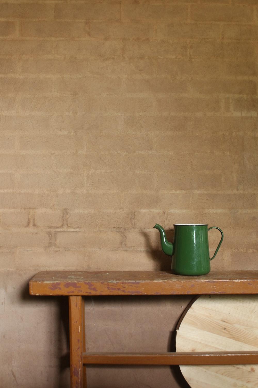green ceramic mug on brown wooden table