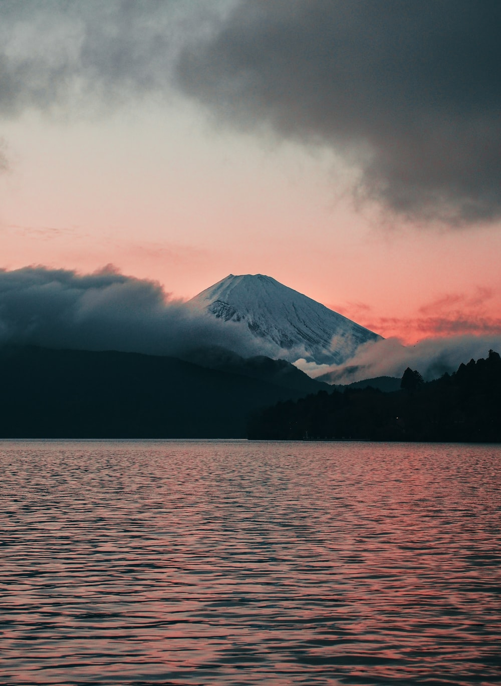 body of water near mountain under cloudy sky during daytime