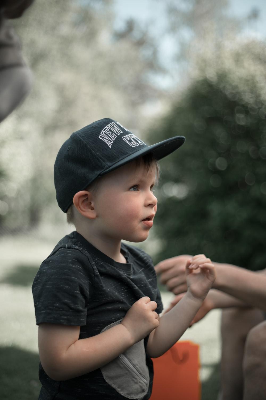 boy in black crew neck t-shirt wearing blue cap