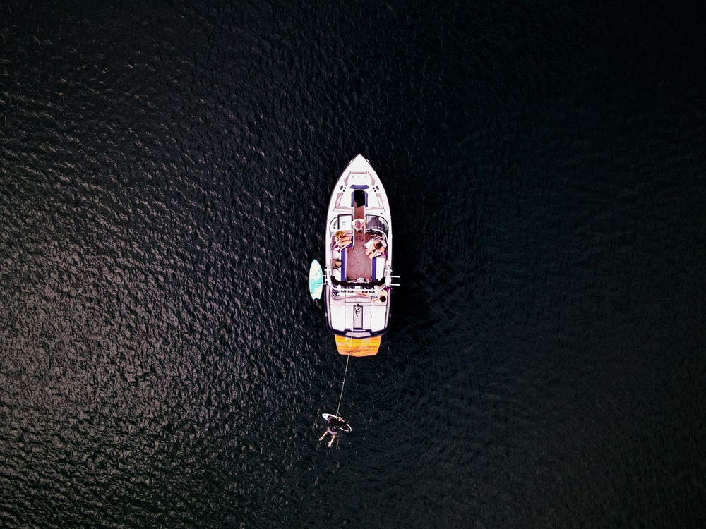 aerial view of white and yellow boat on sea during daytime