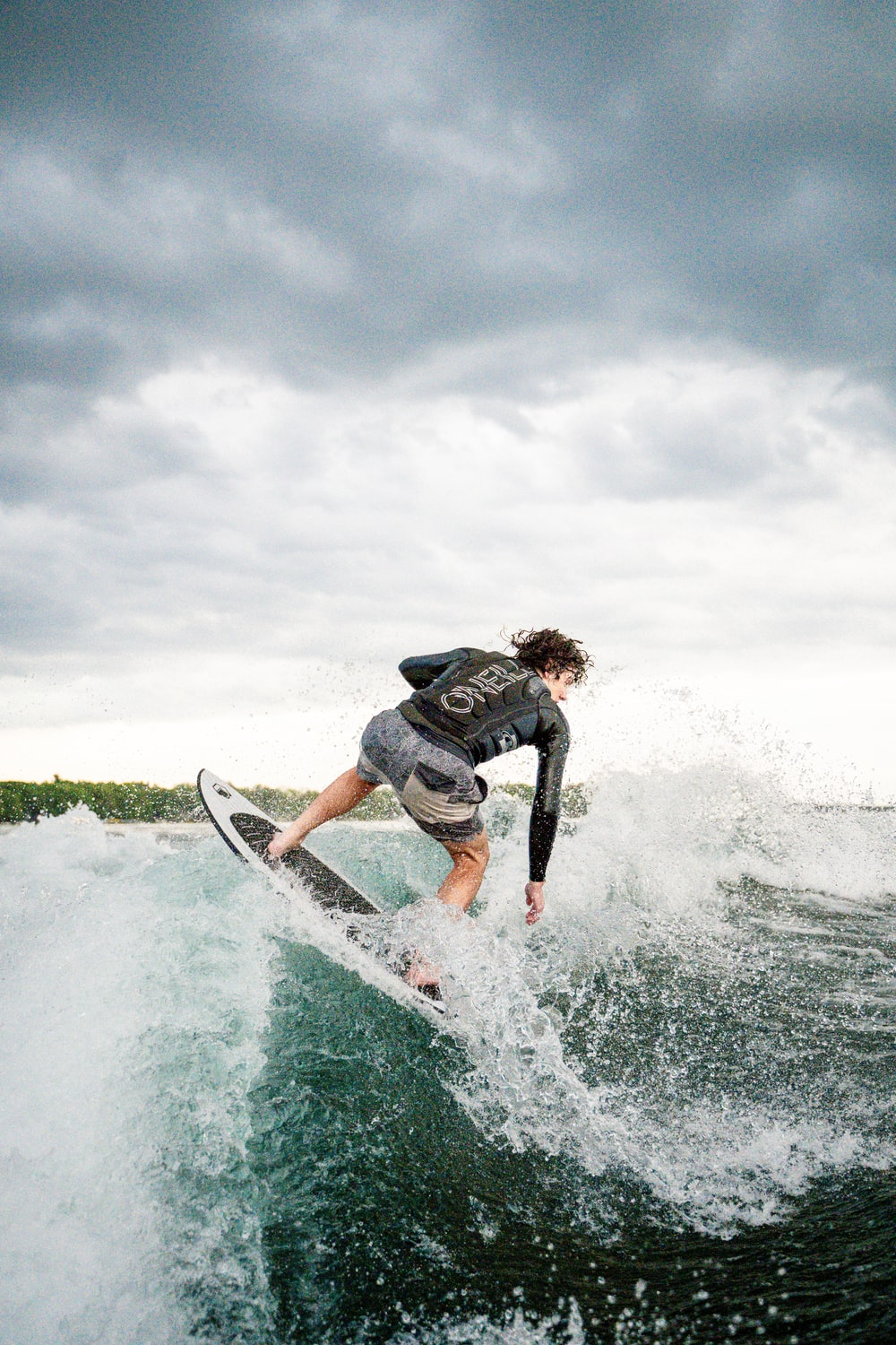 man in black and white wet suit riding white surfboard on sea waves during daytime