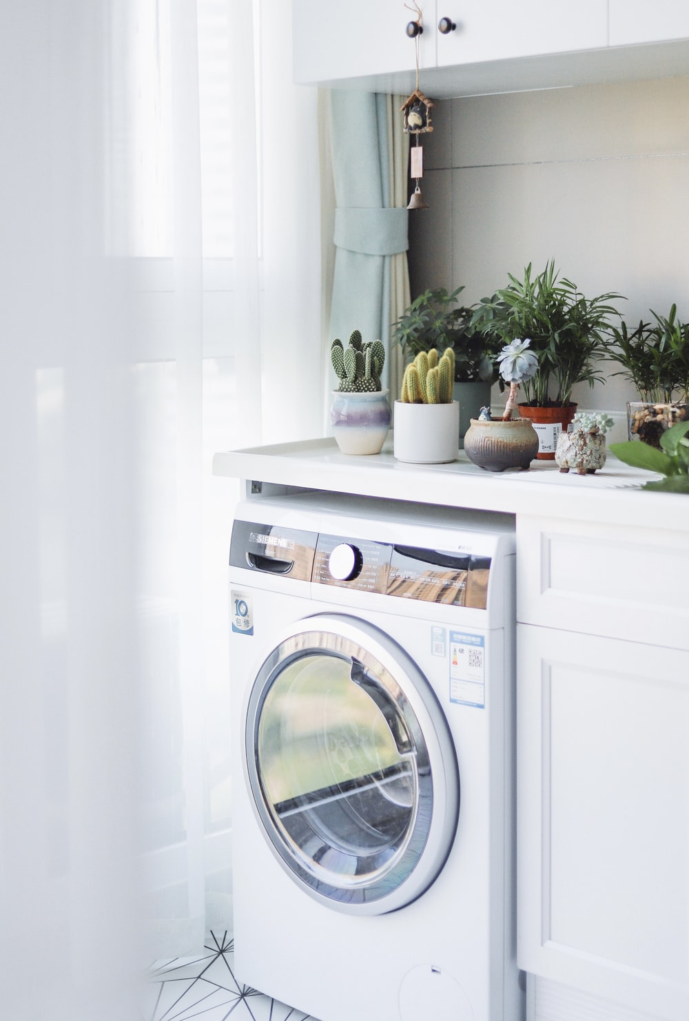 white front load washing machine beside white wooden cabinet