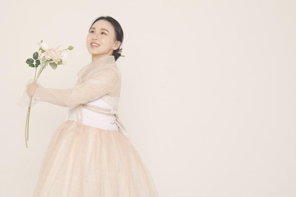 girl in white dress holding white flower