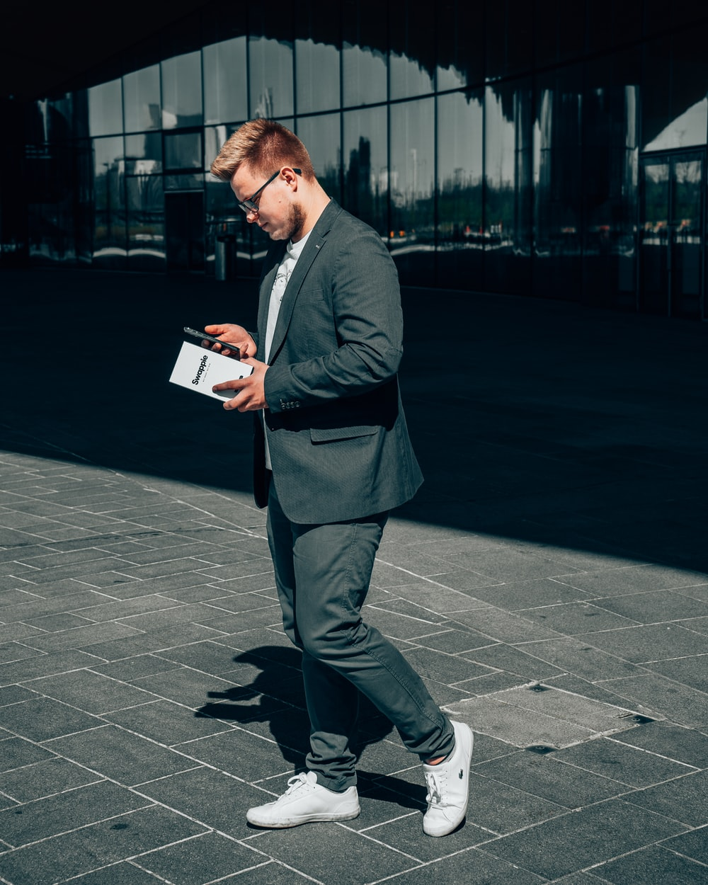 man in black suit jacket and gray pants holding book