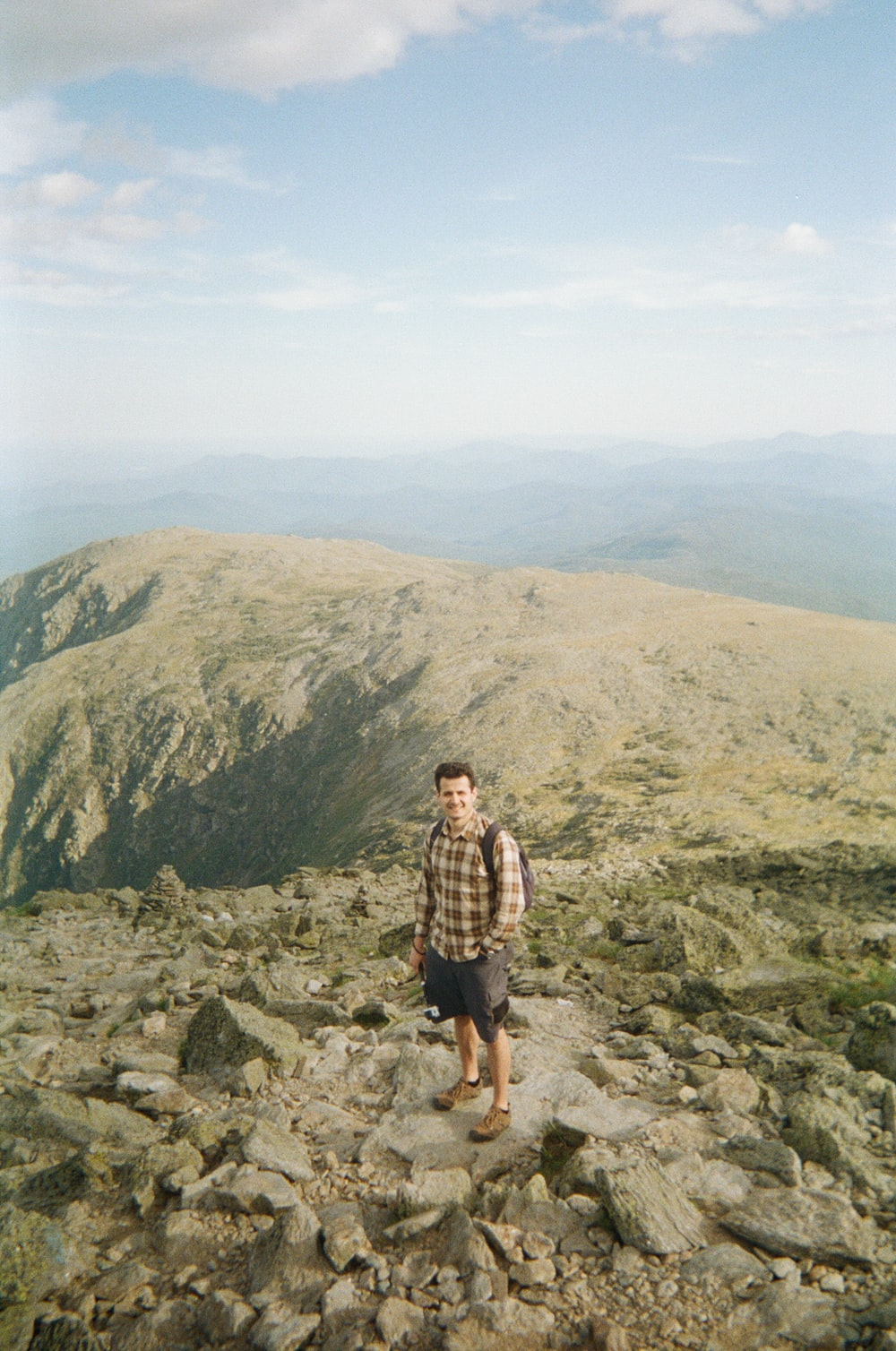 man in brown and black plaid shirt standing on rocky mountain during daytime