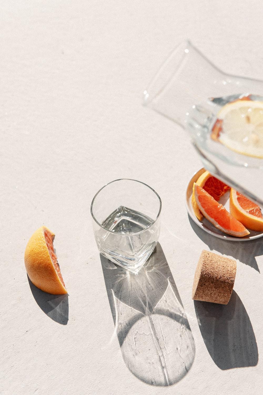 clear drinking glass beside sliced orange fruit