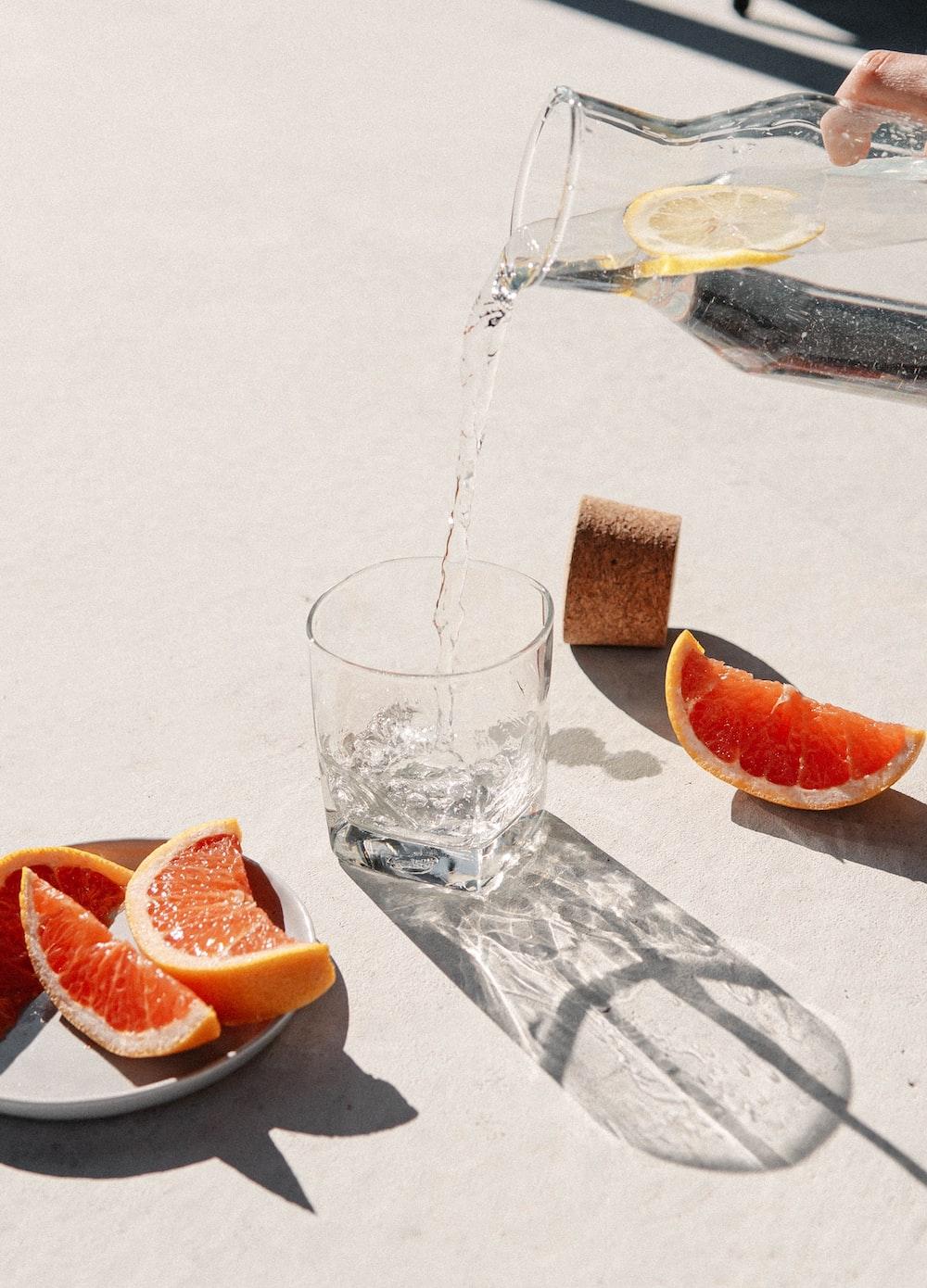 sliced orange fruit beside clear drinking glass