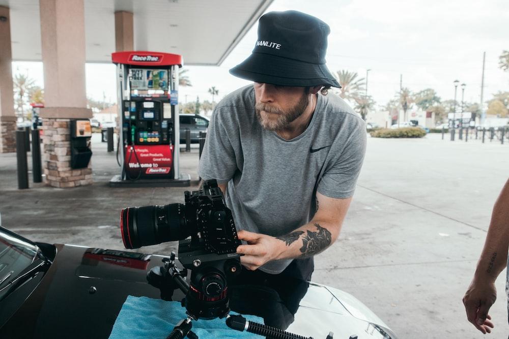 man in gray crew neck shirt and black pants holding black dslr camera