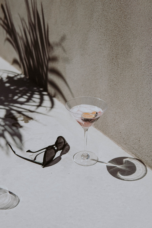 black framed sunglasses beside clear wine glass on white table