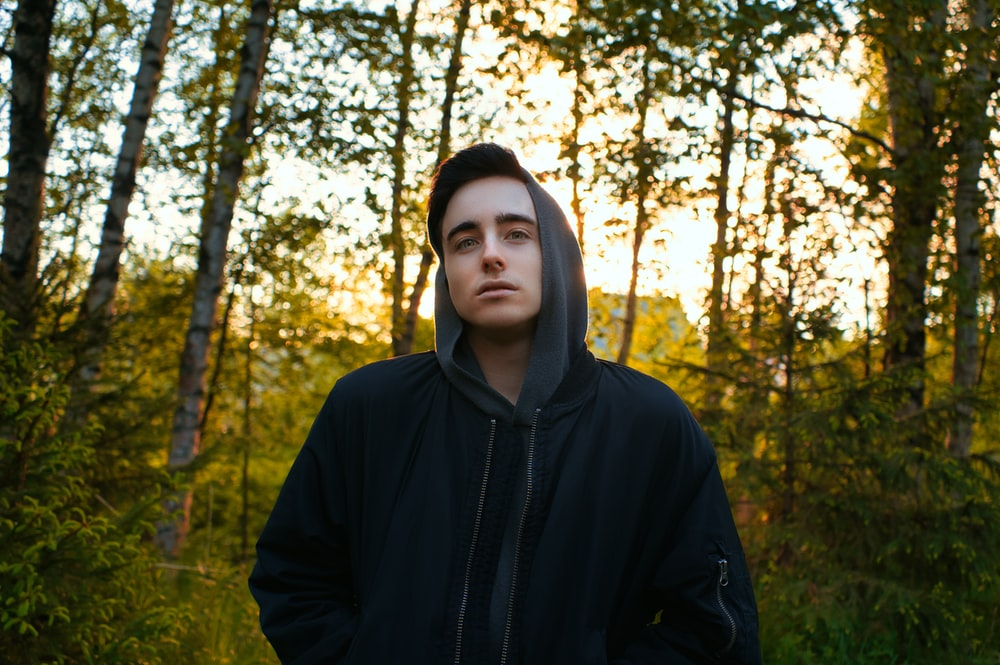 man in black hoodie standing in forest during daytime