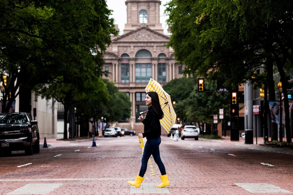 man in black and yellow jacket and black pants walking on sidewalk during daytime