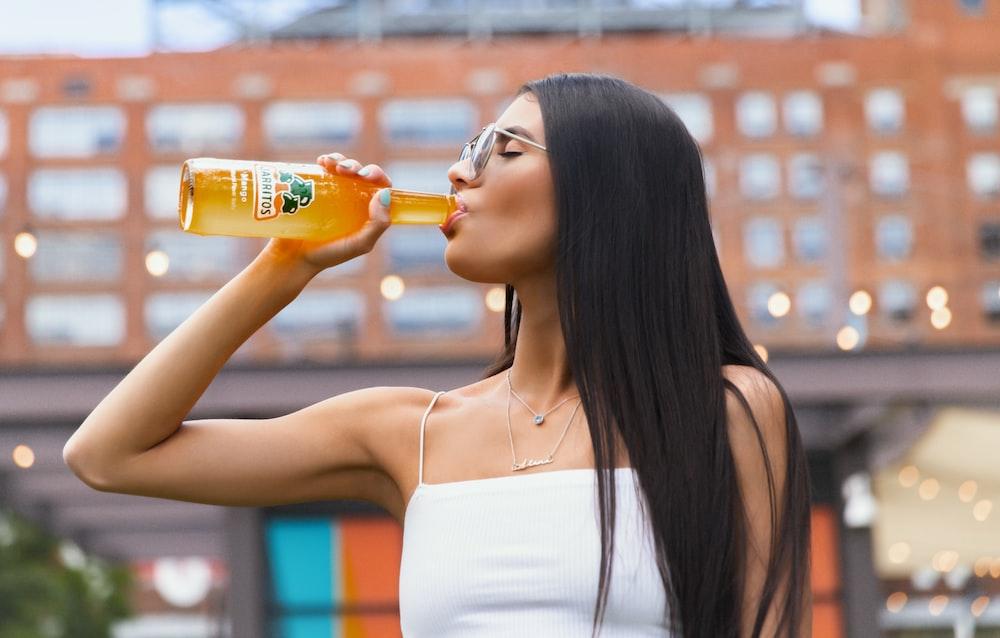 woman in white spaghetti strap top drinking orange bottle