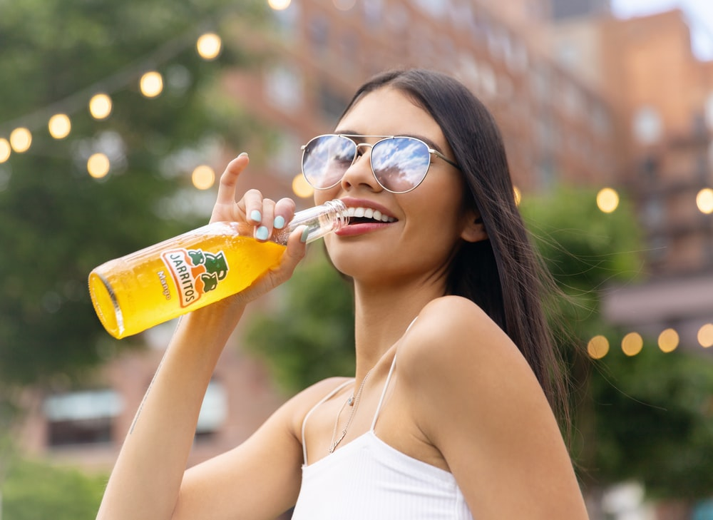 woman in white tank top drinking yellow labeled bottle