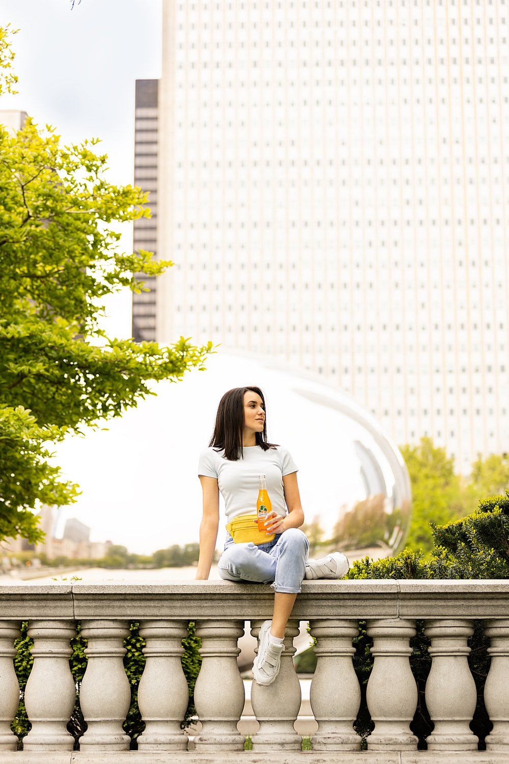 woman in white shirt sitting on gray wooden bench during daytime