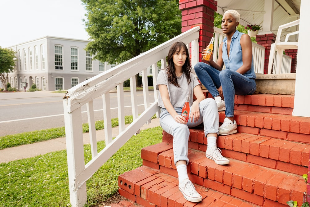 3 women sitting on white wooden fence during daytime