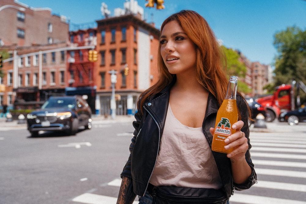 woman in white shirt and black leather jacket holding orange bottle