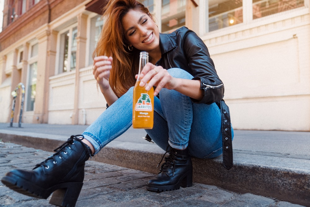 woman in black leather jacket holding orange plastic bottle