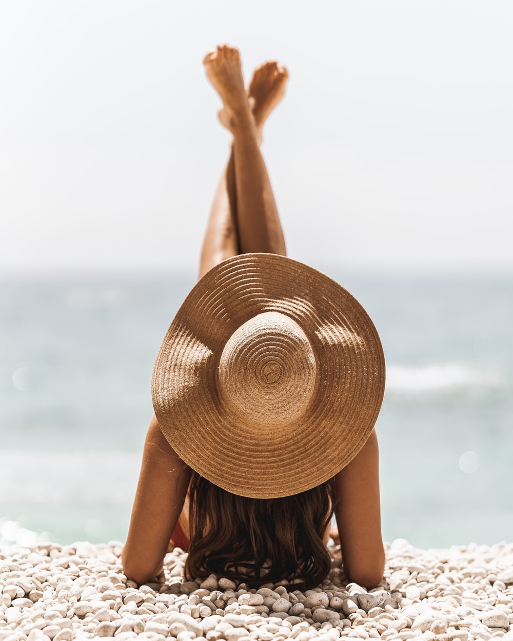 woman in brown sun hat standing on beach during daytime