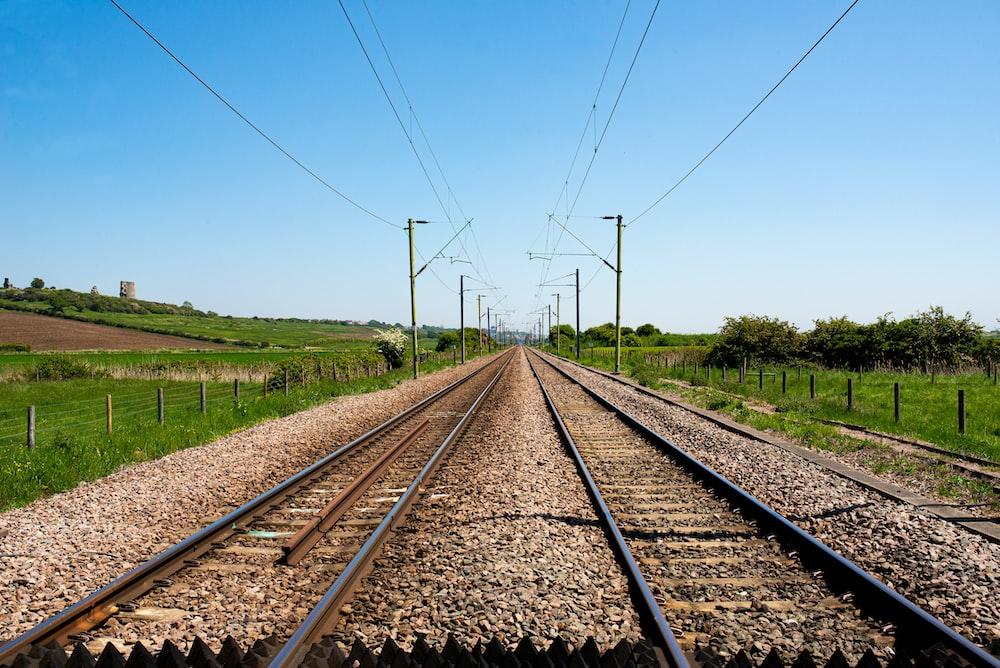 brown train rail near green grass field during daytime
