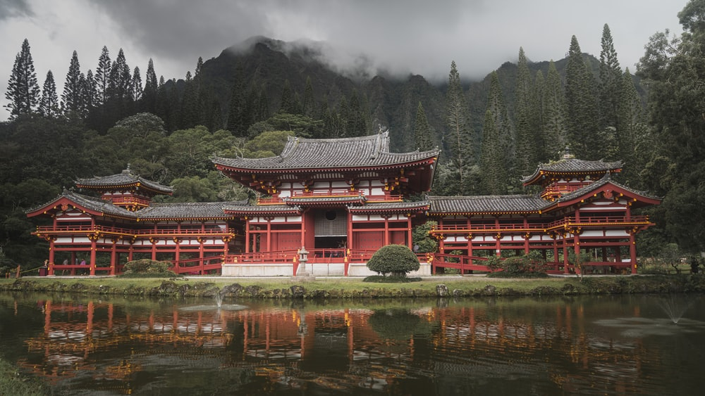 red and white temple near green trees and lake during daytime