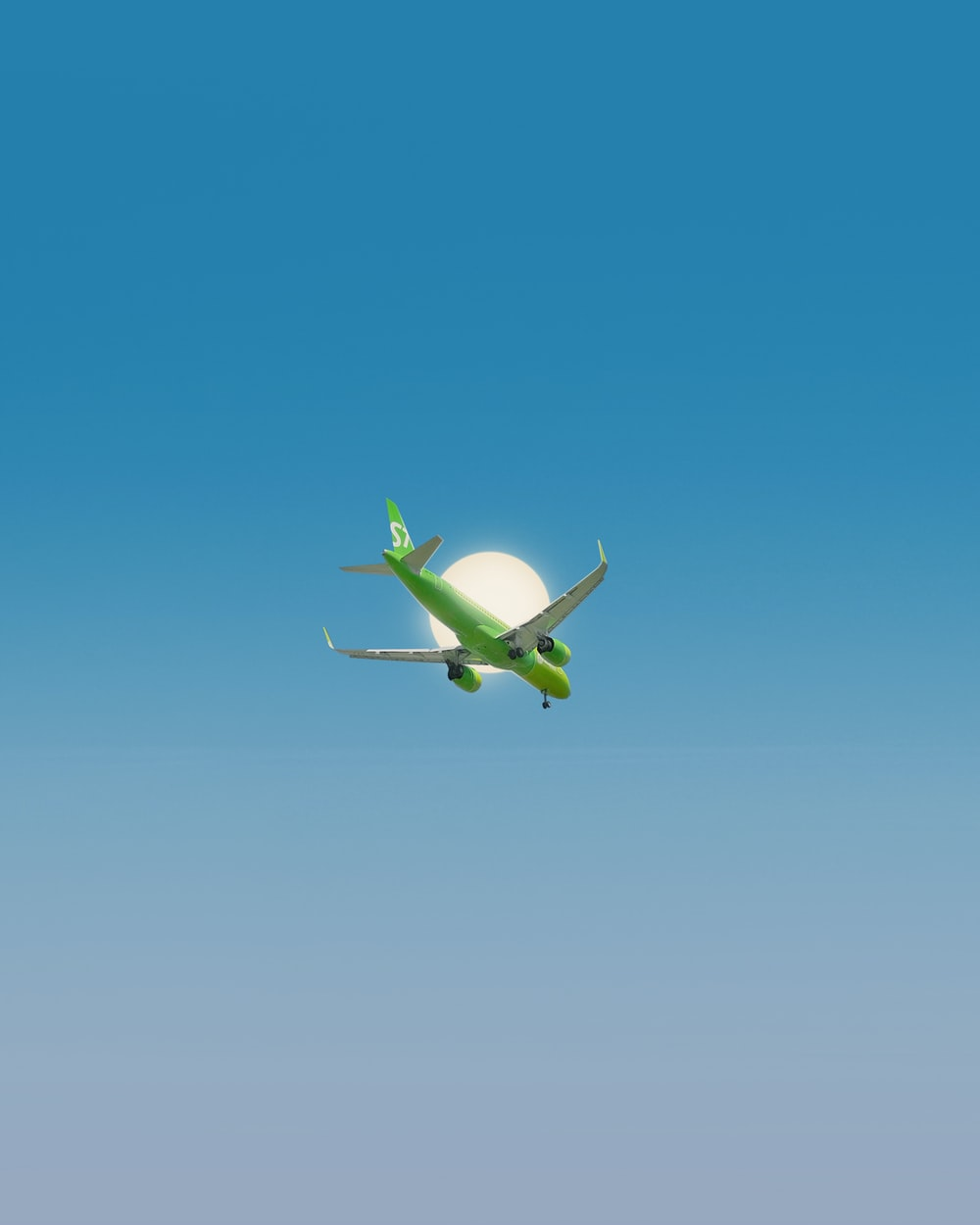 white and green airplane flying under blue sky during daytime