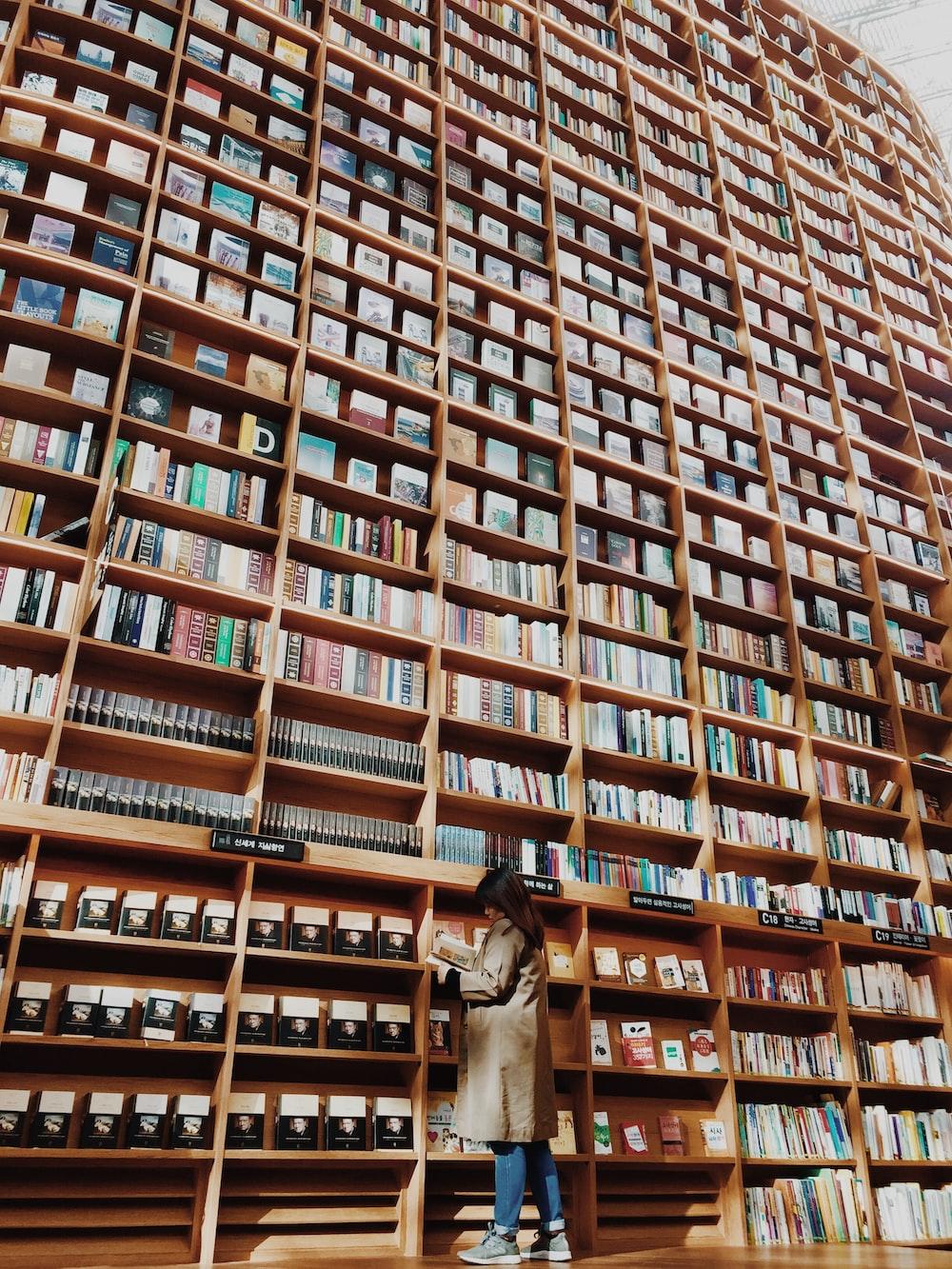 man in brown coat standing in front of brown wooden book shelf