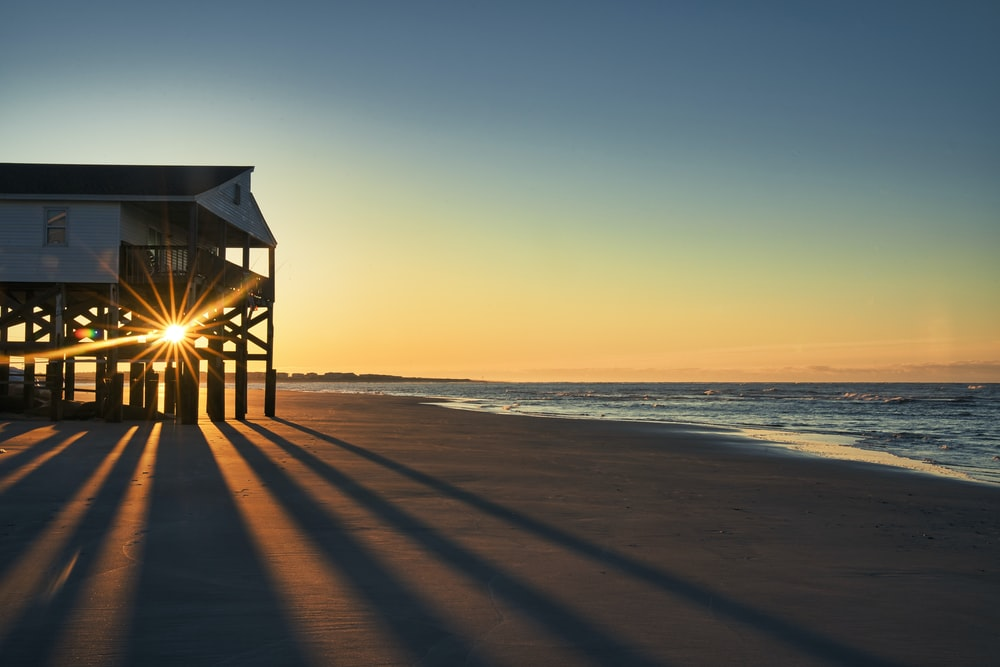 brown wooden house on beach during sunset