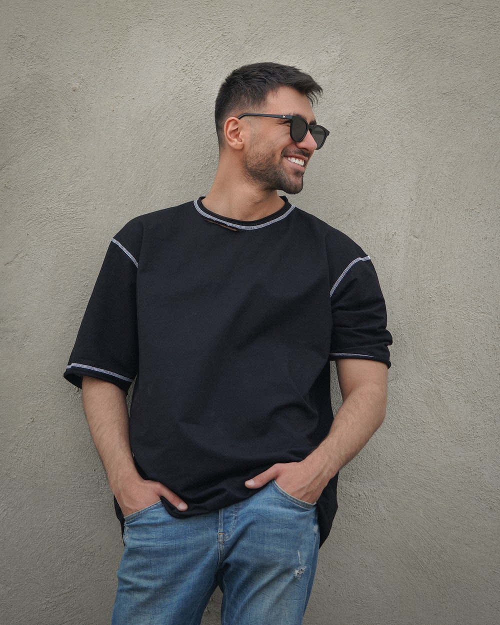 man in black crew neck t-shirt and blue denim jeans standing beside white wall