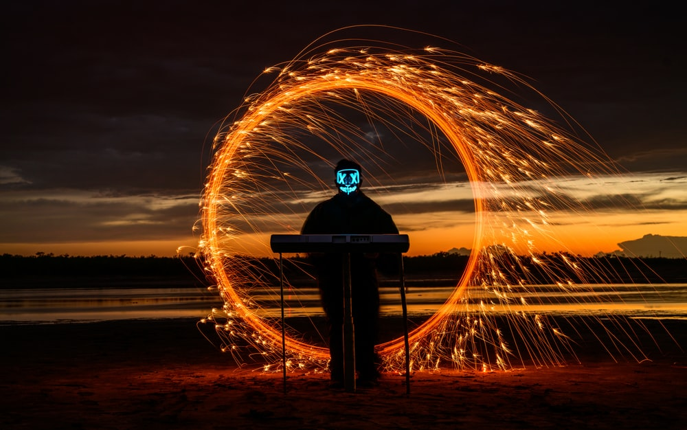 man in black jacket sitting on bench in front of steel wool during night time