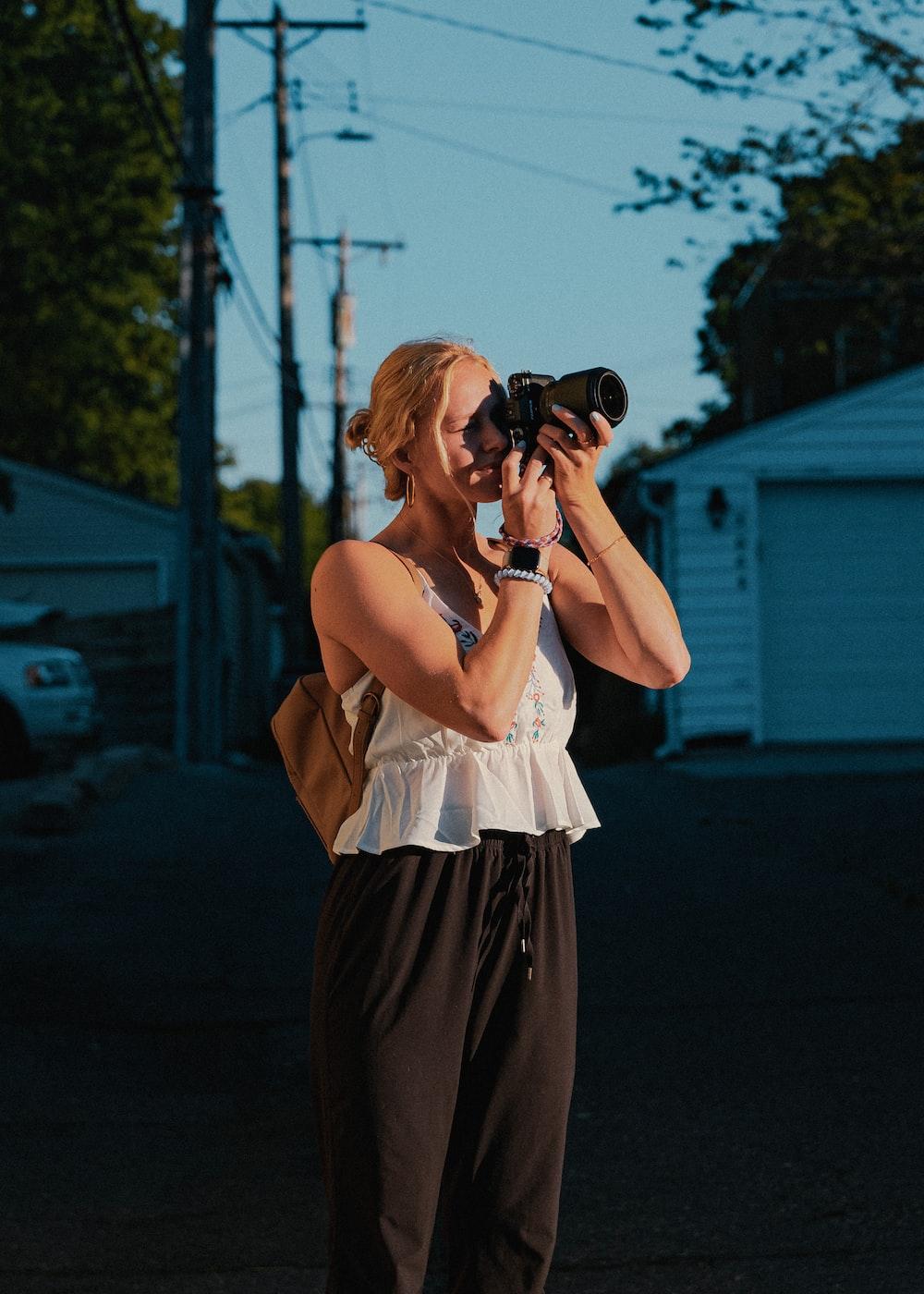 woman in white sleeveless dress holding black dslr camera