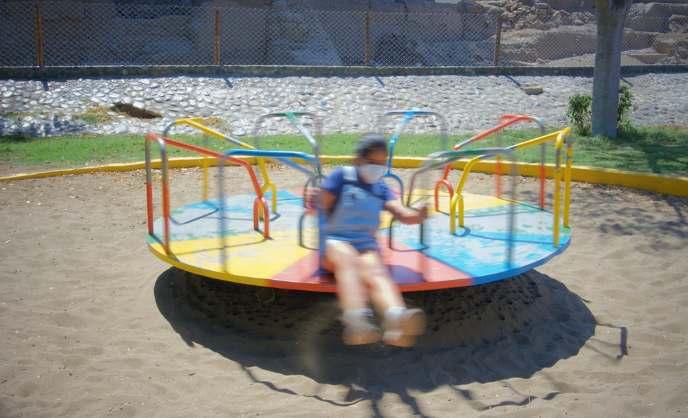 2 children playing on yellow and blue trampoline