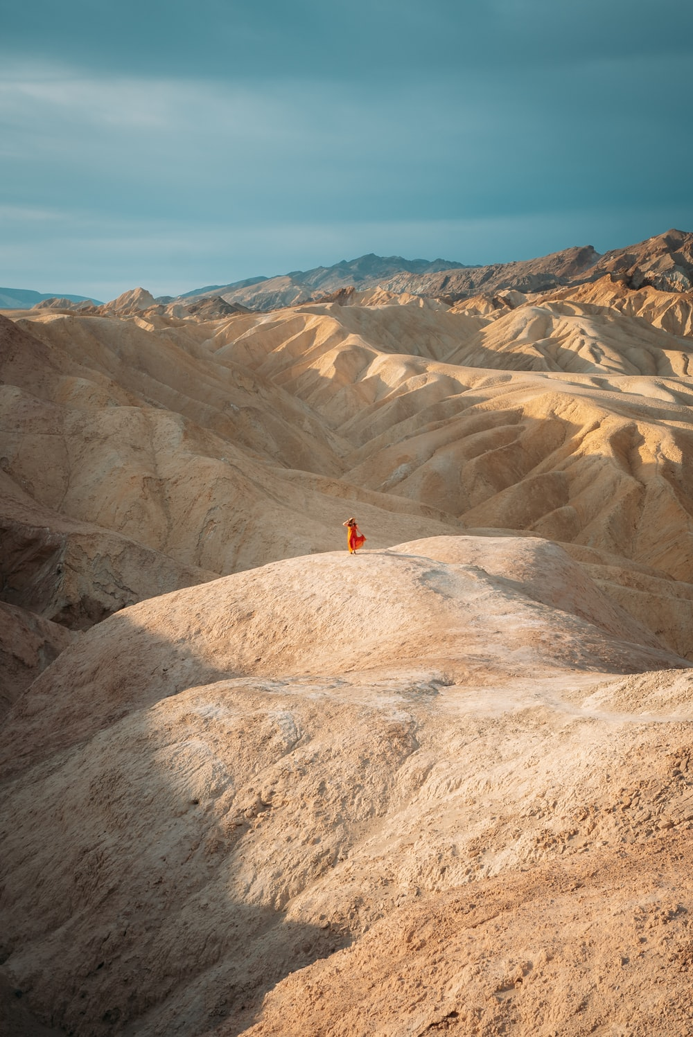 person in red shirt standing on brown rock formation during daytime