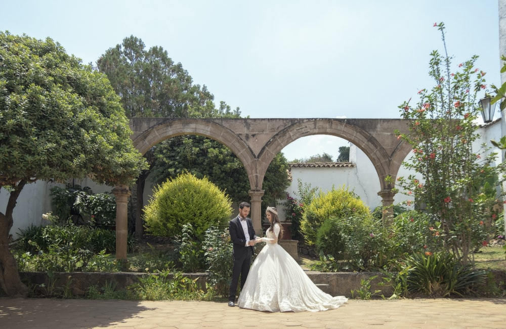 bride and groom standing on brown concrete floor during daytime