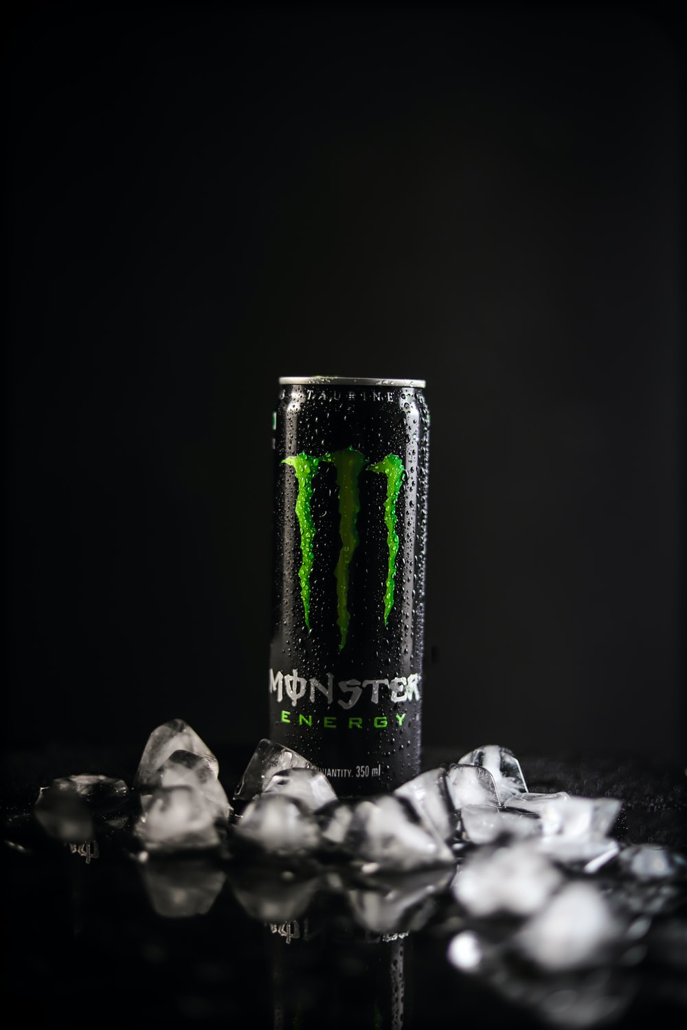 monster energy drink can on black and white textile