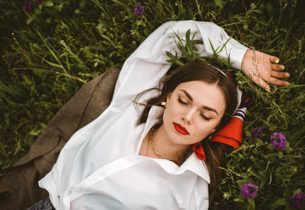 woman in white button up shirt lying on purple flower field during daytime