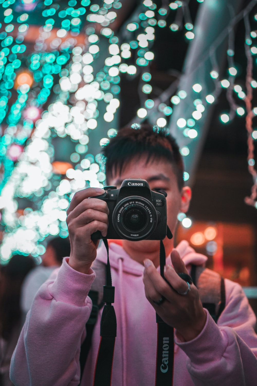 woman in pink jacket holding black nikon dslr camera