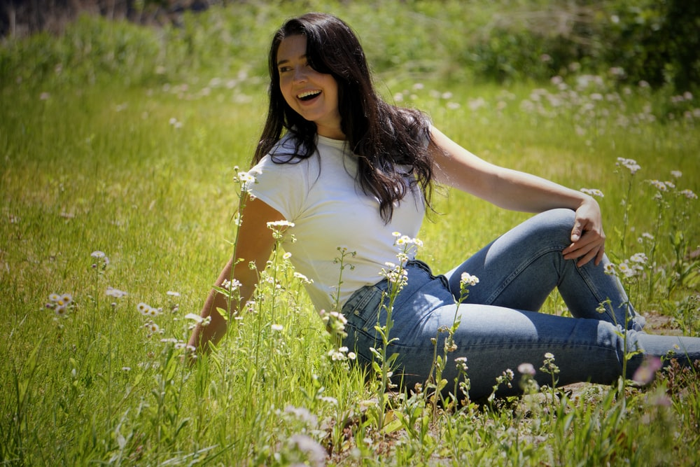 woman in white shirt and blue denim jeans sitting on green grass field during daytime