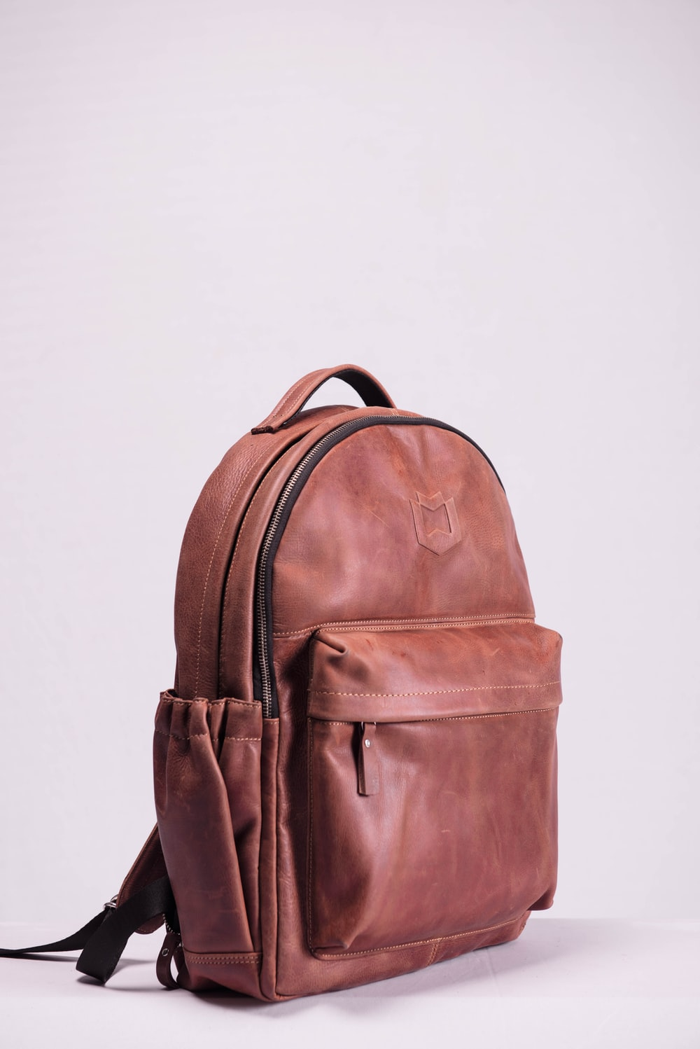 brown leather backpack on white wall
